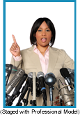African-American woman speaking before a bank of microphones. (Staged with a Professional Model).