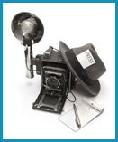Black and white picture of old fashion camera with traditional press hat resting against it.
