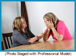 Counselor handing crying woman a tissue. (Photo staged with professional models)