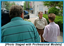 Camerman and woman interviewing a man on the street (staged with professional models).