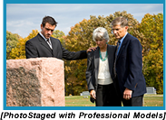 A young man and an older adult couple gazing at a headstone (Staged with professional models).