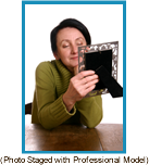 Woman gazing at a photo in a picture frame. (Staged with a professional model).