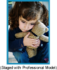 Sad little girl with pony tails hugging a teddy bear.