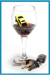 Wine glass with a small yellow toy car partially submerged in the partially filled glass with a set of car keys placed at the bottom of the glass.